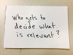 "Note card with ""Who gets to decide what is relvant?"" in black."